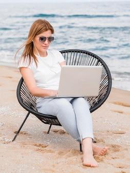 Vista frontal de la mujer que trabaja en la computadora portátil en la silla de playa