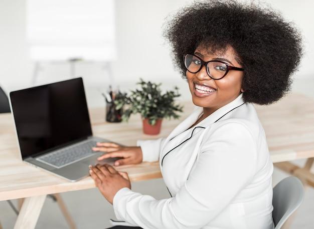 Vista frontal de la mujer que trabaja en la computadora portátil