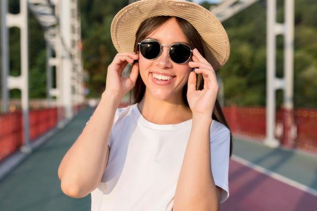 Vista frontal de la mujer que viaja sonriente en el puente con sombrero y gafas de sol