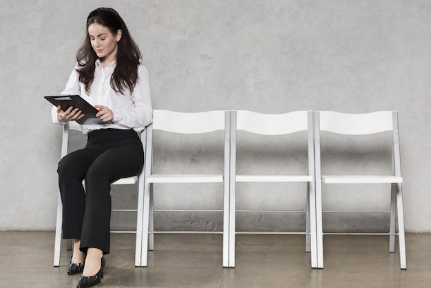 Vista frontal de la mujer de recursos humanos analizando currículum