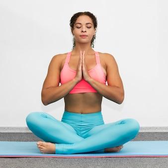 Vista frontal mujer relajante en estera de yoga