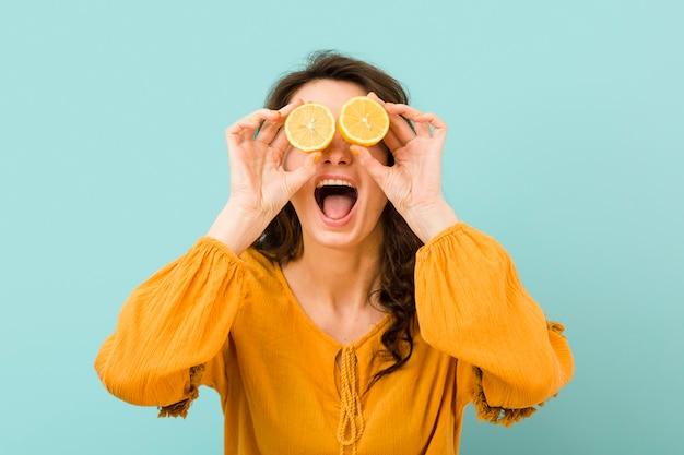 Vista frontal de la mujer con rodajas de limón