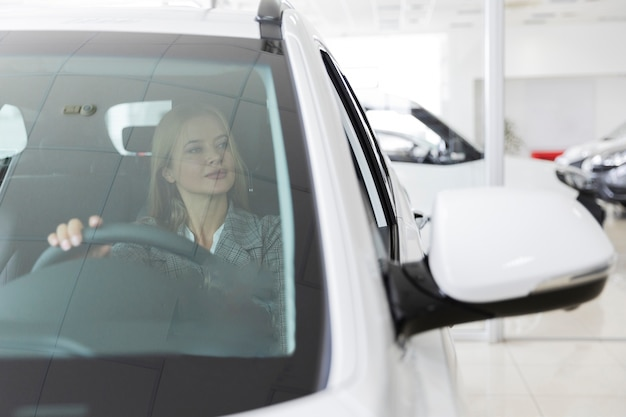 Vista frontal de una mujer rubia en el auto
