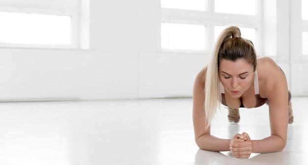 Vista frontal de la mujer rubia haciendo tablón