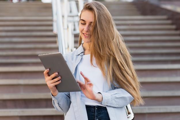 Vista frontal mujer rubia usando una tableta