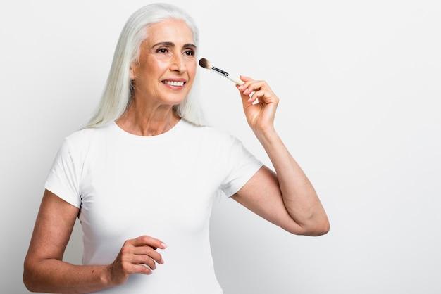 Vista frontal de mujer senior con pincel de maquillaje