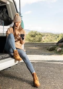 Vista frontal de una mujer sentada en el maletero del coche durante un viaje por carretera y sosteniendo la cámara