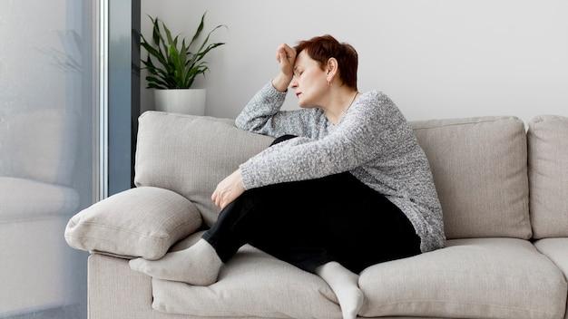 Vista frontal de la mujer sentada en el sofá