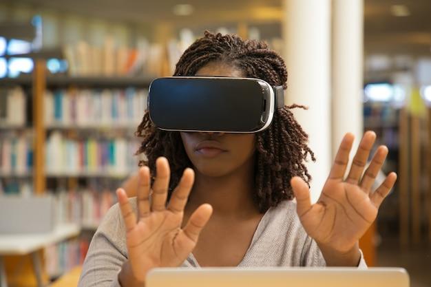 Vista frontal de una mujer seria con gafas de realidad virtual