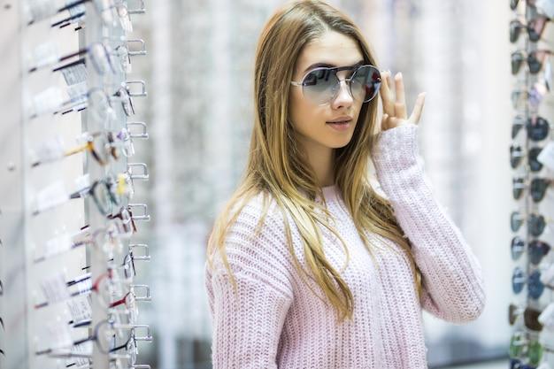Vista frontal de la mujer seria en suéter blanco pruebe gafas en tienda profesional en