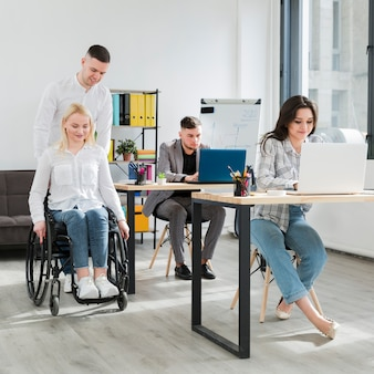 Vista frontal de la mujer en silla de ruedas ayudada por un compañero de trabajo en la oficina