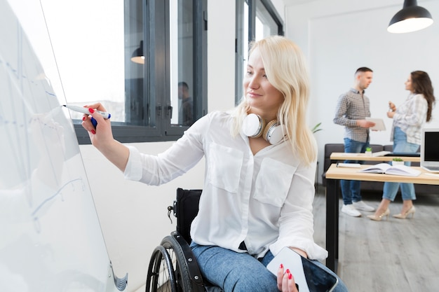 Vista frontal de la mujer en silla de ruedas escribiendo en la pizarra en el trabajo