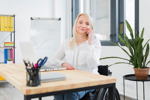 Vista frontal de la mujer en silla de ruedas posando mientras habla por teléfono en el trabajo