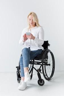 Vista frontal de la mujer en silla de ruedas con smartphone