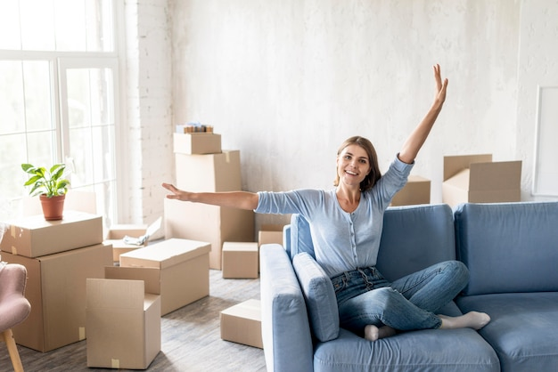 Vista frontal de la mujer en el sofá feliz de mudarse