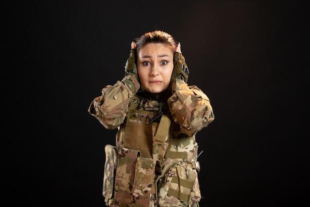 Vista frontal de la mujer soldado asustada en camuflaje en la pared negra
