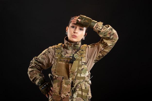 Vista frontal de la mujer soldado cansada en camuflaje en la pared negra