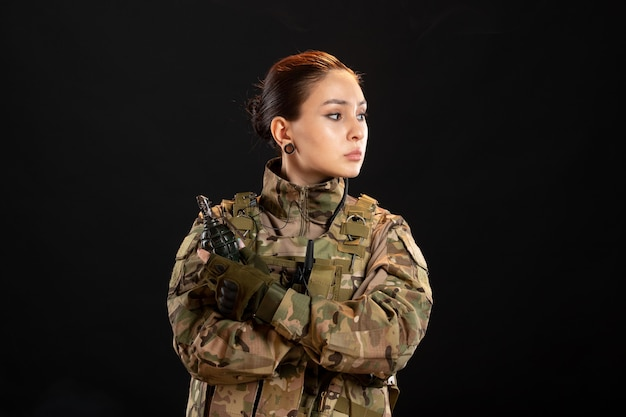Vista frontal de la mujer soldado con granada en uniforme sobre pared negra