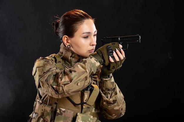 Vista frontal de la mujer soldado con pistola en estudio uniforme en pared negra