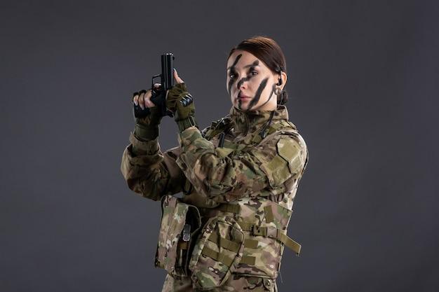 Vista frontal de la mujer soldado con pistola en pared oscura de camuflaje