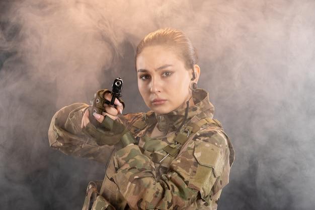 Vista frontal de la mujer soldado con pistola en uniforme en la pared ahumada negra