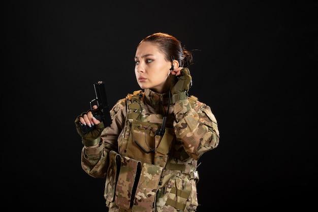 Vista frontal de la mujer soldado con pistola en uniforme sobre pared negra
