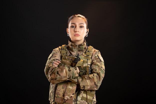 Vista frontal de la mujer soldado seria en camuflaje en la pared negra