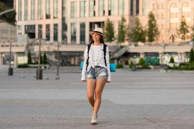 Vista frontal de la mujer con sombrero llevando mochila mientras viaja solo
