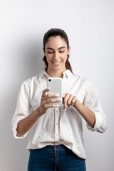 Vista frontal de la mujer sonriendo y sosteniendo el teléfono inteligente