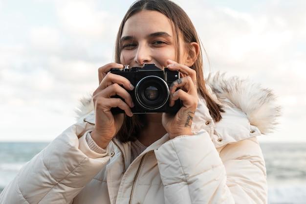 Vista frontal de la mujer sonriente con cámara en la playa.