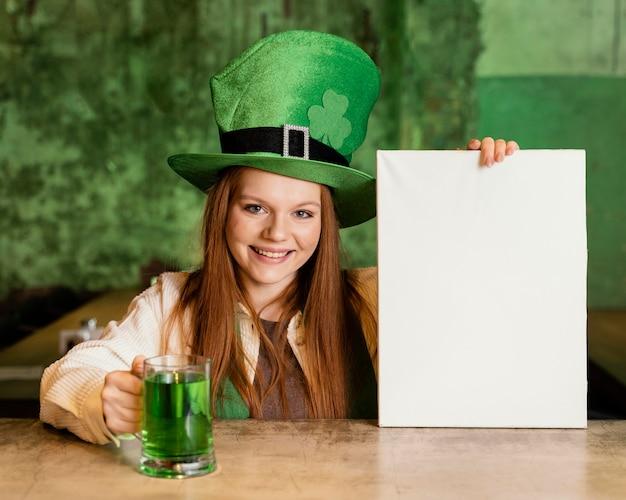 Vista frontal de la mujer sonriente celebrando st. día de patricio en el bar con cartel en blanco y bebida.