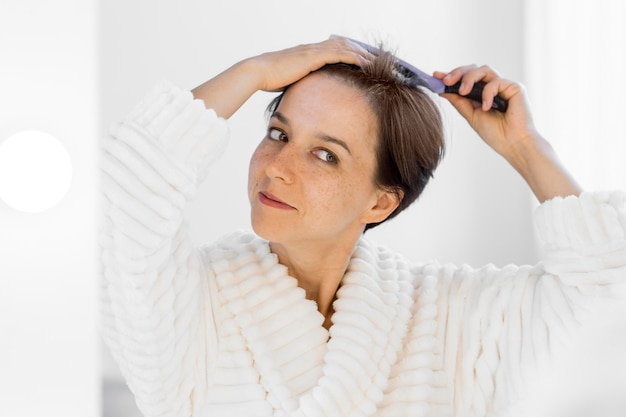 Vista frontal mujer sonriente cepillando su cabello