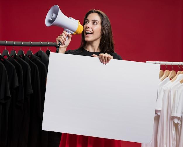 Vista frontal mujer sonriente en compras gritando con un megáfono