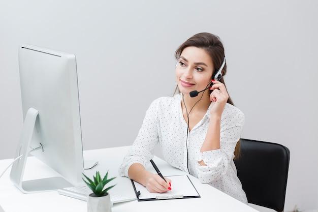 Vista frontal de la mujer sonriente escribiendo algo mientras habla por auriculares