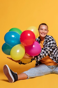 Vista frontal de la mujer sonriente con globos