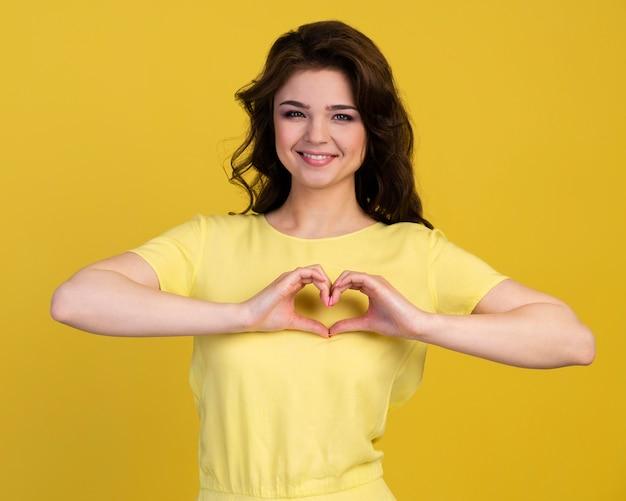 Vista frontal de la mujer sonriente haciendo signo de corazón con las manos