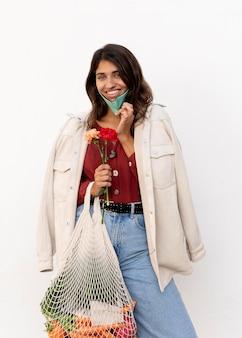 Vista frontal de la mujer sonriente con mascarilla y bolsas de la compra.