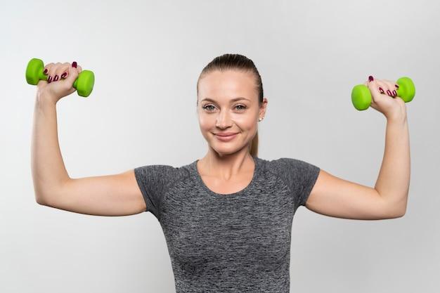 Vista frontal de la mujer sonriente con pesas de fisioterapia