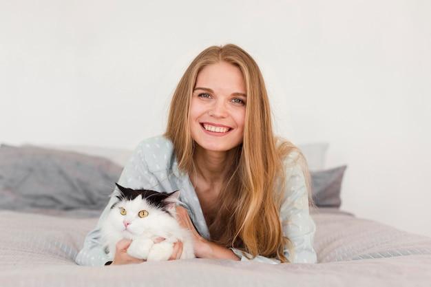 Vista frontal de la mujer sonriente en pijama en casa en la cama con gato