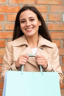 Vista frontal de la mujer sonriente posando con bolsas de la compra.