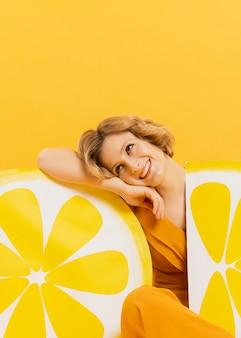 Vista frontal de la mujer sonriente posando con decoraciones de rodajas de limón