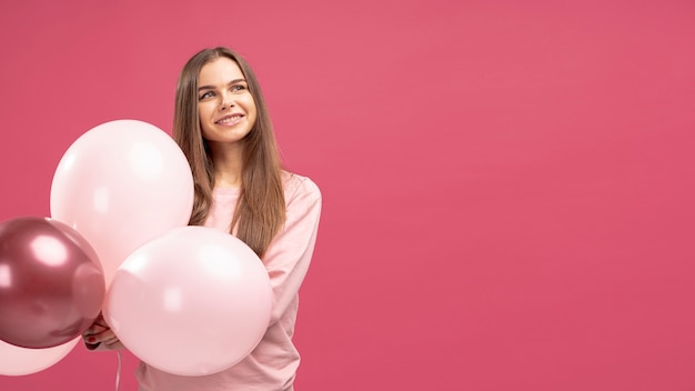 Vista frontal de la mujer sonriente posando con globos