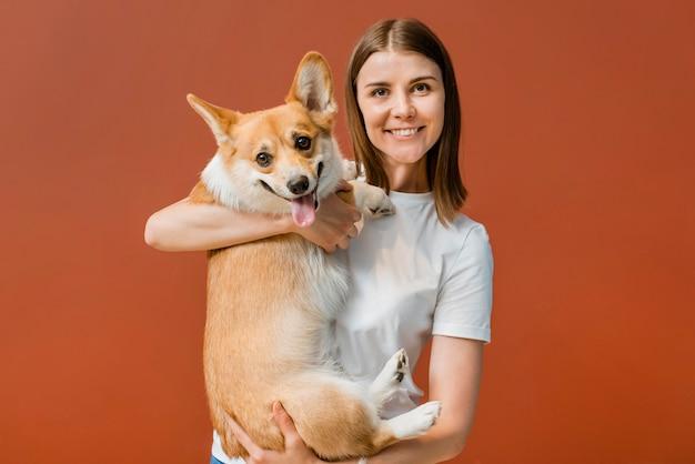 Vista frontal de la mujer sonriente posando con su lindo perro