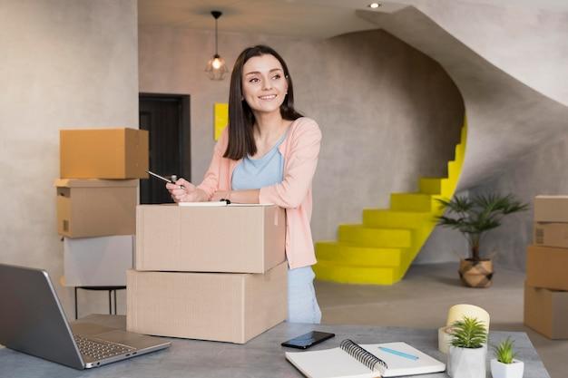 Vista frontal de la mujer sonriente preparando cajas para entrega