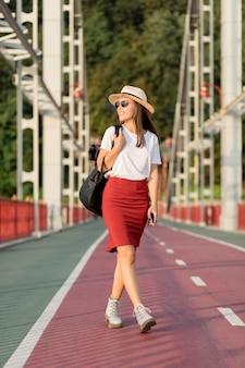 Vista frontal de la mujer sonriente en el puente con gafas de sol mientras viaja
