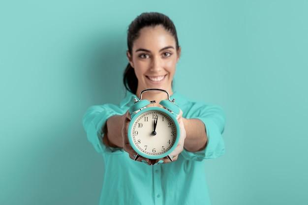 Vista frontal de la mujer sonriente que sostiene el reloj