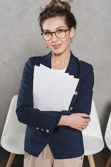 Vista frontal de la mujer sonriente de recursos humanos con papeles