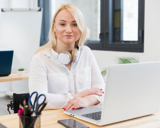 Vista frontal de la mujer sonriente en silla de ruedas posando en su escritorio