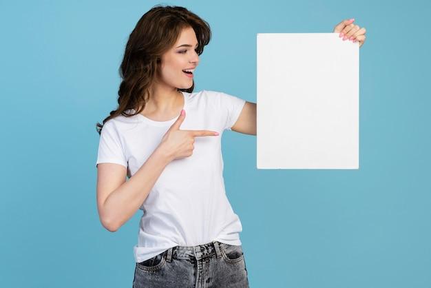 Vista frontal de la mujer sonriente sosteniendo y apuntando al cartel en blanco