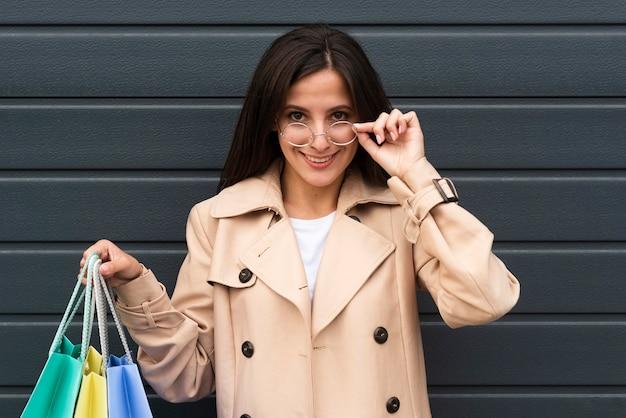 Vista frontal de la mujer sonriente sosteniendo bolsas de la compra.